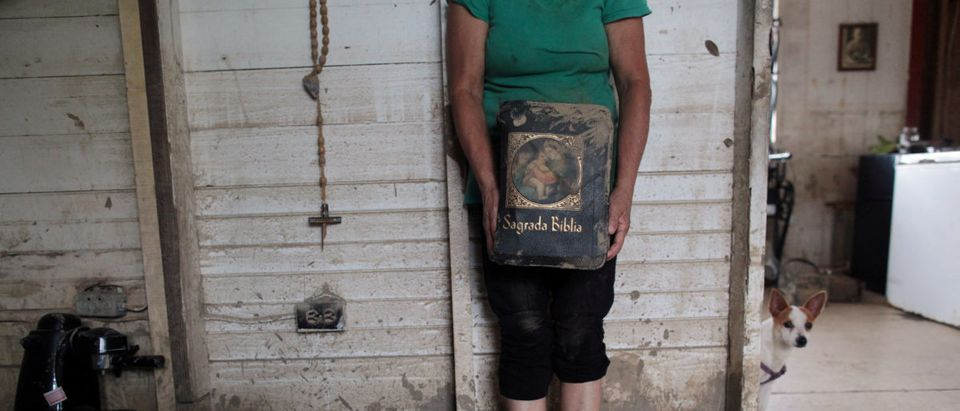 Aurea Esther Gonzalez holds a bible dirty with mud, after Hurricane Maria hit the island in September, in Toa Baja, Puerto Rico October 18, 2017. REUTERS/Alvin Baez