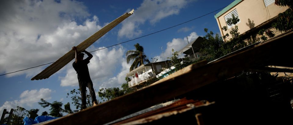 Carlos Ventura carries a corrugated metal sheet to be used for a ceiling, while he helps a neighbour to rebuild her house, which was partially destroyed by Hurricane Maria, at the squatter community of Villa Hugo in Canovanas, Puerto Rico, December 9, 2017. Villa Hugo is a settlement initially formed by people whose houses were damaged or destroyed by Hurricane Hugo in 1989. REUTERS/Carlos Garcia Rawlins