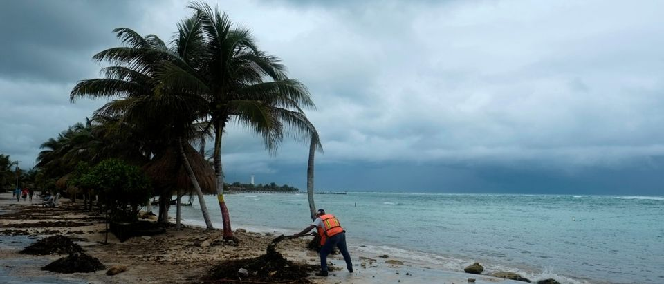 A worker cleans the beach of branches and debris after the passing of Tropical Storm Franklin in Majahual in the state of Quintana Roo