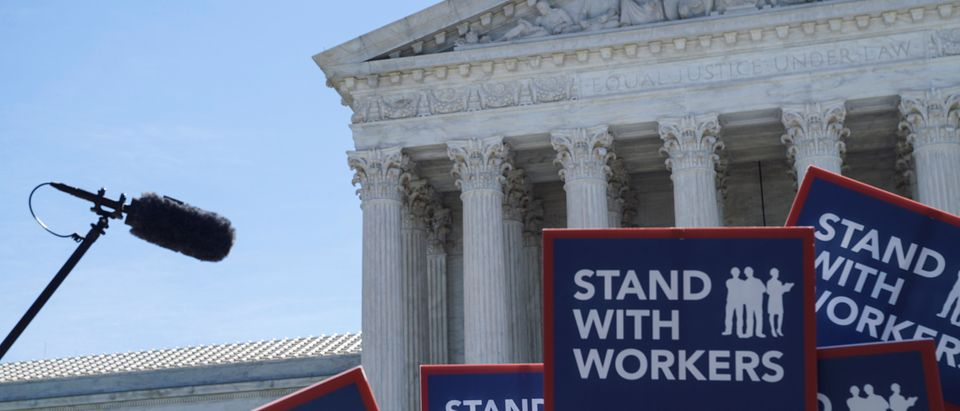 People hold signs outside the U.S. Supreme Court, waiting for the Janus v. American Federation of State, County, and Municipal Employees case in Washington