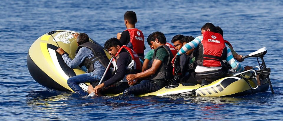 Migrants in a dinghy with a small motor paddle their craft after leaving Bodrum, Turkey, in the hopes of crossing the Mediterranean Sea