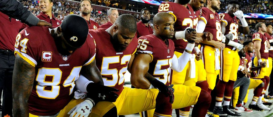 FILE PHOTO: Washington Redskins players kneel during the playing of the national anthem