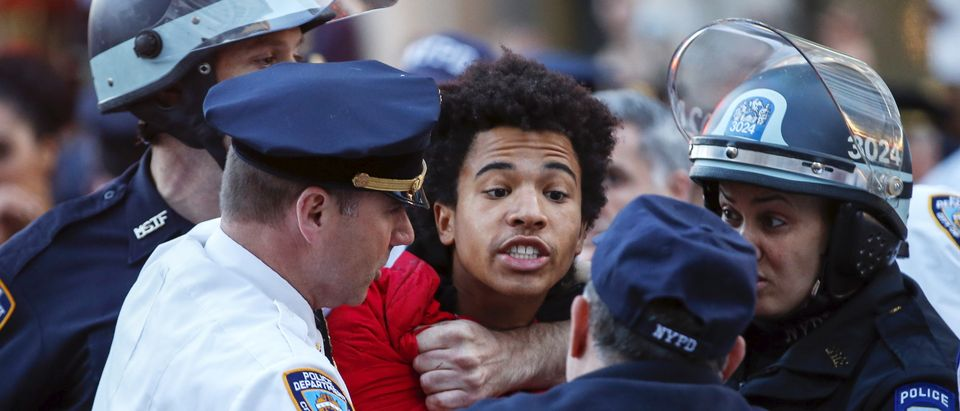 NYPD officers detain a protester during a march through the Manhattan borough of New York City