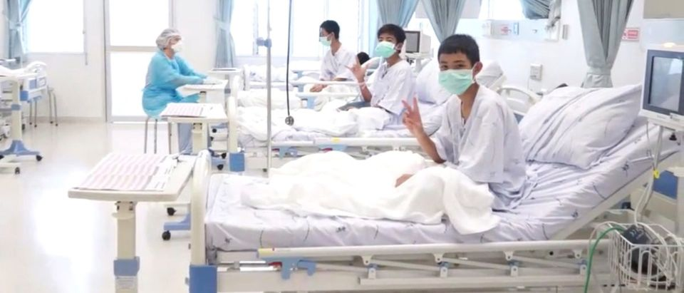 A screen grab shows boys rescued from the Thai cave wearing mask and resting in a hospital in Chiang Rai