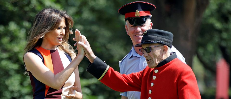 "U.S. First Lady Melania Trump high-fives with a British military veteran known as a ""Chelsea Pensioner"" during a game of bowls at The Royal Hospital Chelsea in central London"
