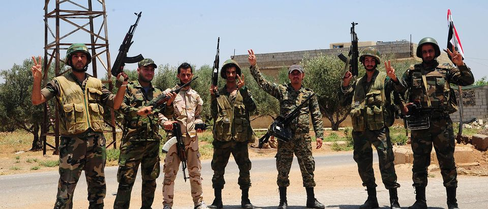 Syrian army soldiers gesture as they pose for a picture in Deraa area