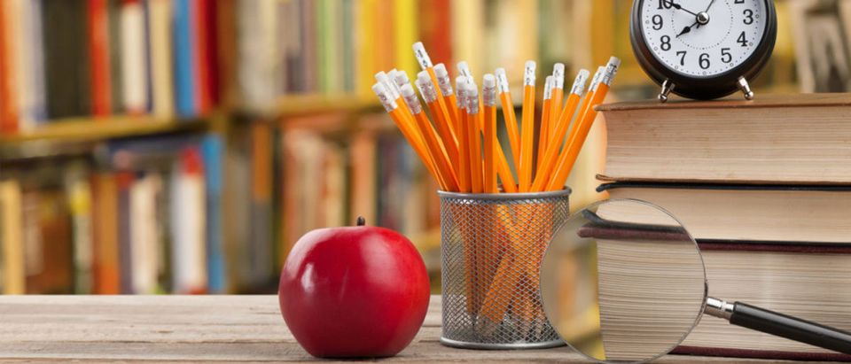 Books, pencils, and a desk are featured at school. (Shutterstock/Billion Photos)
