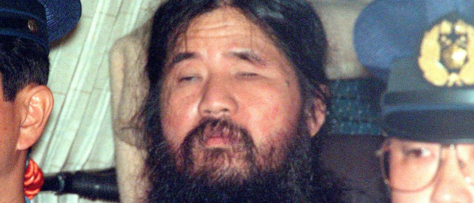 Japanese doomsday cult leader Shoko Asahara sits in a police van following an interrogation in Tokyo, Japan, in this photo taken by Kyodo September 25, 1995. Mandatory credit Kyodo/via REUTERS