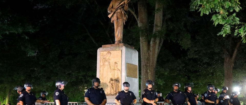 Police wearing riot gear guard a statue of a Confederate soldier nicknamed Silent Sam on the campus of the University of North Carolina during a demonstration for its removal in Chapel Hill, North Carolina, U.S. August 22, 2017. REUTERS/Jonathan Drake -