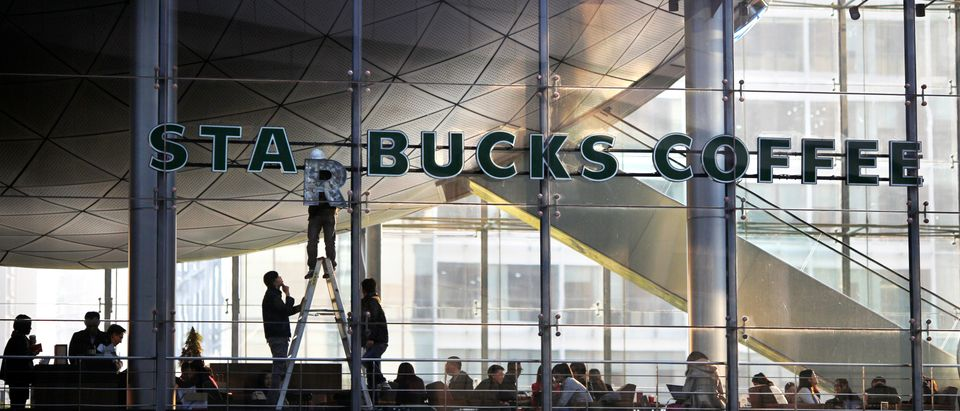 FILE PHOTO: Workers install a letter of a Starbucks sign at a Starbucks coffee store inside a building in Shanghai November 17, 2014. REUTERS/Carlos Barria/File Photo