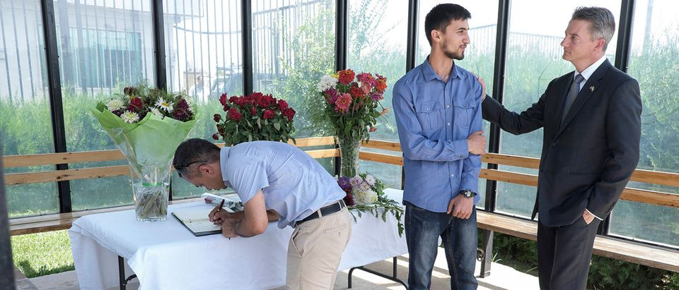 The United States Charge dAffaires, Kevin Covert (R) speaks with a man as people come to pay their tribute to the victims of a deadly attack, at the US Embassy in Dushanbe on July 31, 2018. - Two US, a Swiss and a Dutch citizens, were struck by a car and attacked on July 29 while on a popular cycle route in the Danghara district, about 100 kilometres (60 miles) south of the capital Dushanbe. Police in Tajikistan on March 31 appeared to blame a banned opposition party for an attack previously claimed by the Islamic State group that left four tourists dead and was originally reported as a hit-and-run road accident. STR/AFP/Getty Images