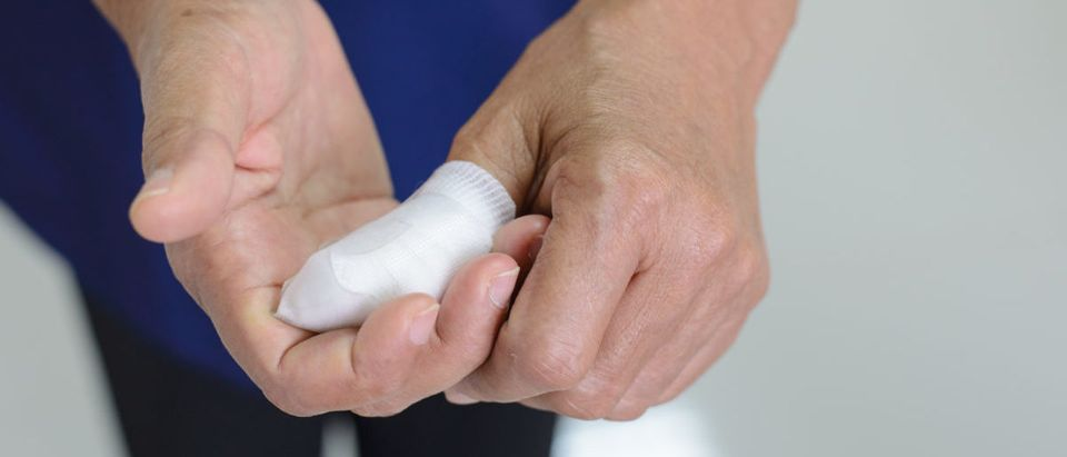 The thumb is wrapped with a bandage, which is first aid on a white background. ShutterStock Gee363