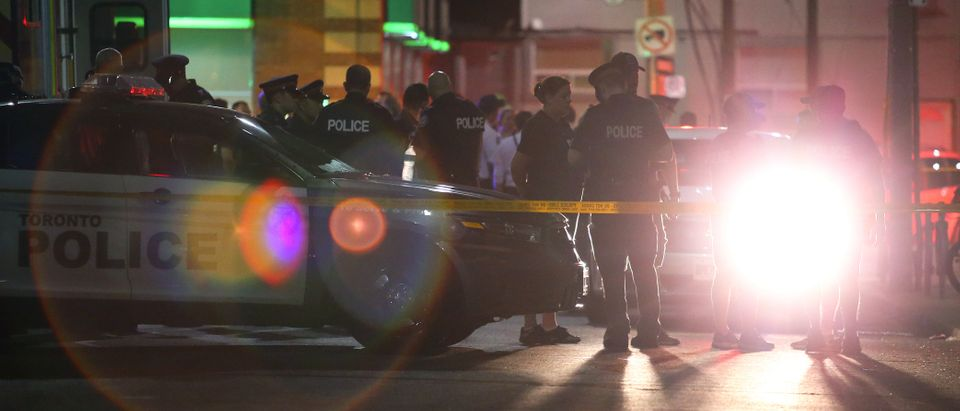 Police officers attend the scene of a mass shooting in Toronto