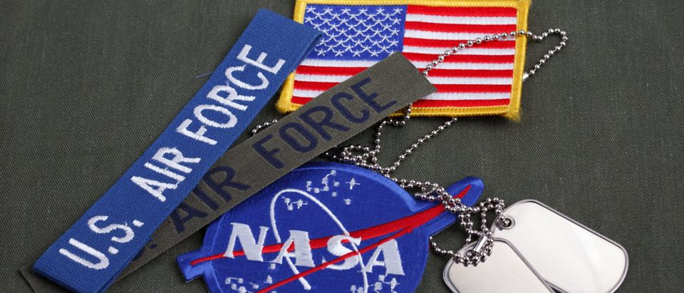 15 March 2018 - The National Aeronautics and Space Administration (NASA) emblem patch, dog tags, US AIR FORCE branch tape and US Flag patch on green uniform background. Image: Shutterstock.com