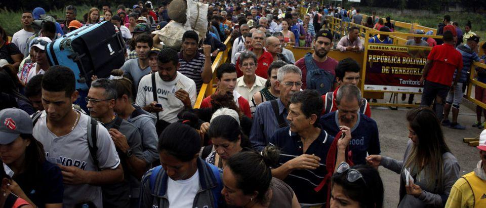 People cross the Colombian-Venezuelan border over the Simon Bolivar international bridge, Colombia June 27, 2018. REUTERS/Carlos Eduardo Ramirez