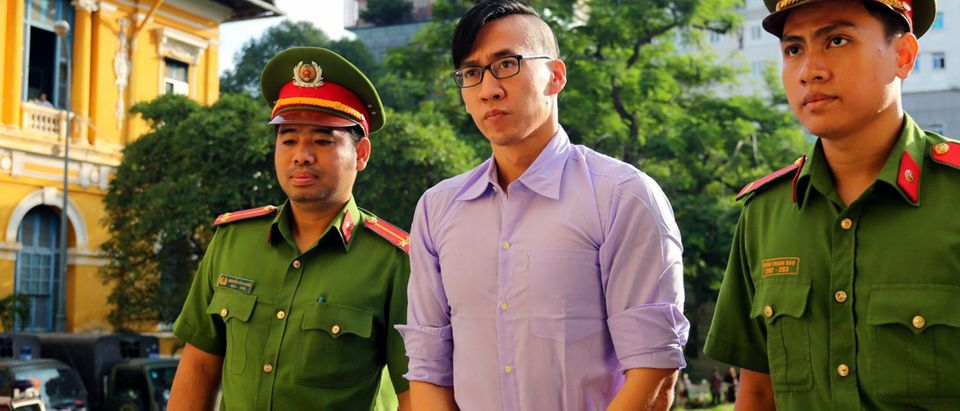 US citizen Will Nguyen is escorted by policemen before his trial at a court in Ho Chi Minh city