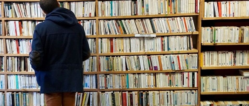 A man examines books in a bookshop on April 2, 2018 during a second-hand books fair in Becherel, western France. (DAMIEN MEYER/AFP/Getty Images)