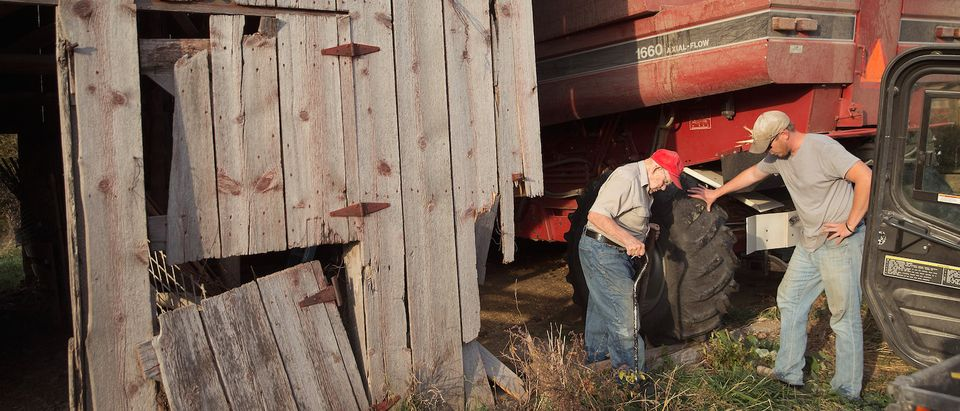 John Anderson (R) helps his 93-year-old great uncle Lyman Howe after Howe finished combining corn on a family farm on October 22, 2015 near Burlington, Iowa. Howe, who has farmed his entire life, now lives in a nursing home but his family picks him each day so he can continue to work on the farm. (Photo: Scott Olson/Getty Images)