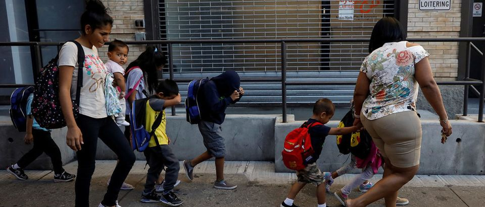 Children cover their faces as they are escorted to the Cayuga Center, which provides foster care and other services to immigrant children separated from their families, in New York