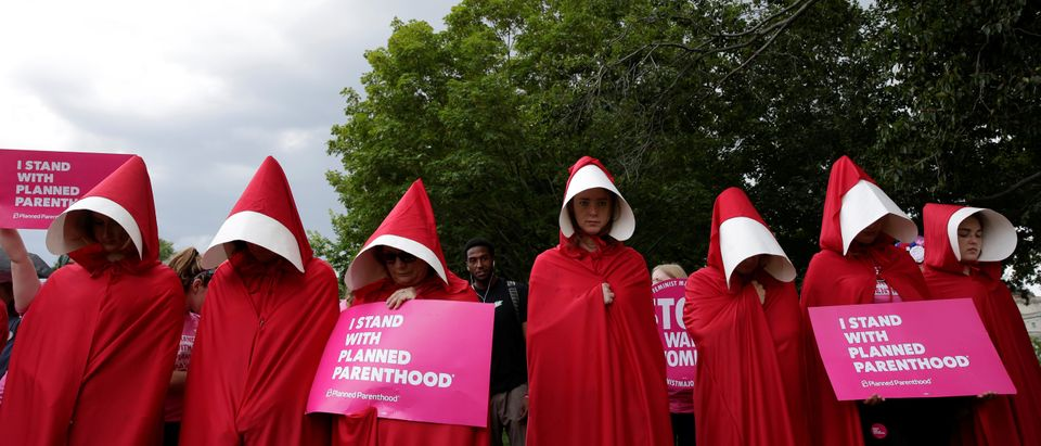 "Women dressed as handmaids from the novel, film and television series ""The Handmaid's Tale"" demonstrate against cuts for Planned Parenthood in the Republican Senate healthcare bill at the U.S. Capitol in Washington, U.S., June 27, 2017. REUTERS/Joshua Roberts"