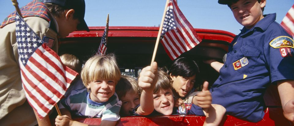 CIRCA 1993 - Cub Scouts waving American flags from back of car, Los Angeles, California / Shuttertsock