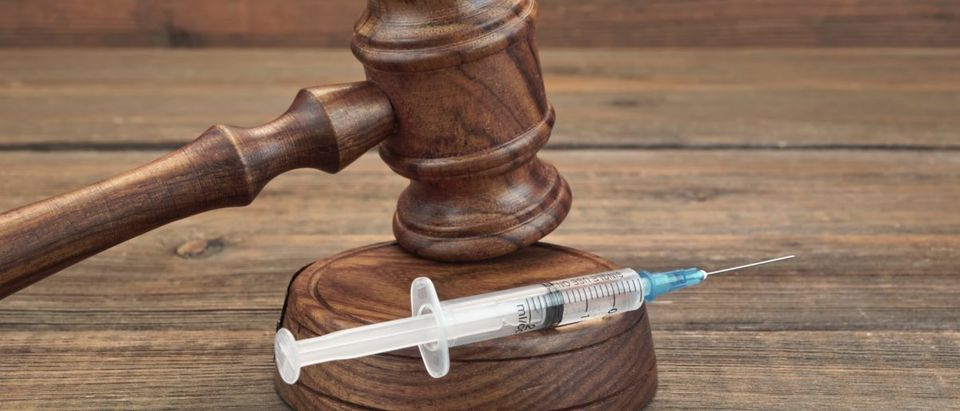 A syringe rests near a gavel. Image via Shutterstock user AVN Photo Lab