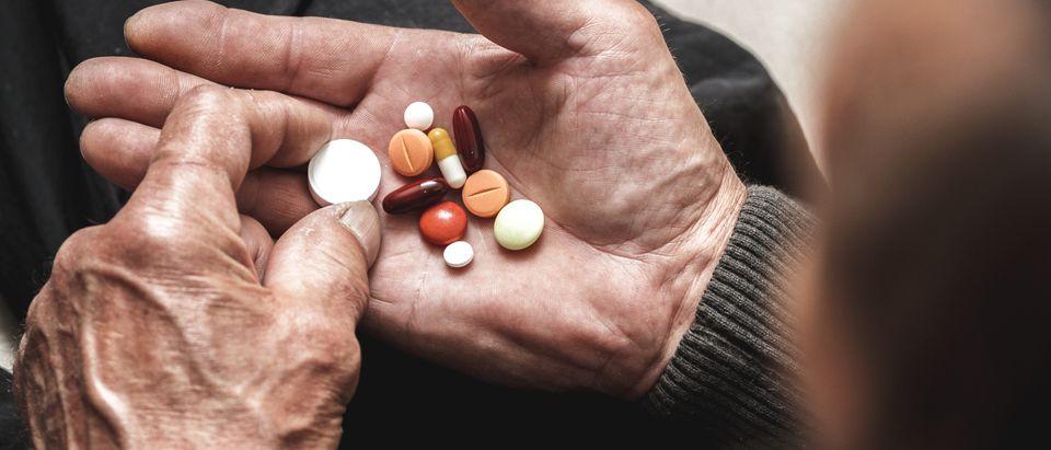 An elderly patient examines pills. Image via Shutterstock user perfectlab