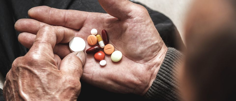 An elderly patient examines pills. Image from Shutterstock via user perfectlab