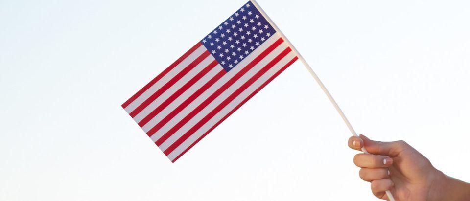 A person waves a U.S. flag. Image via Shutterstock user Pressmaster