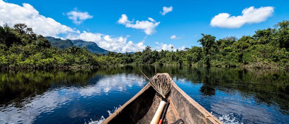 A boat floats down the Amazon River. Shutterstock image via user Douglas Olivares