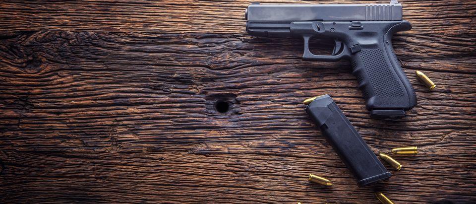 9 mm pistol gun and bullets strewn on the rustic oak table. (Marian Weyo/Shutterstock)