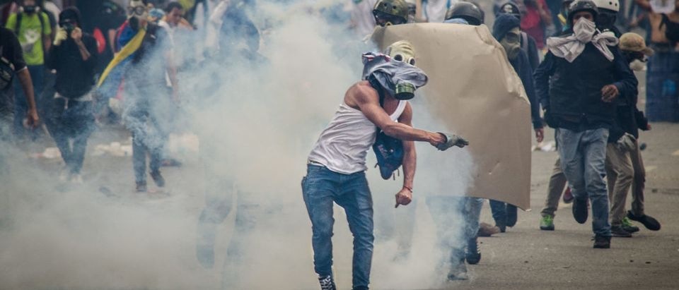 CARACAS, VENEZUELA - APRIL 26, 2017: Protest in Caracas, Venezuela against the government of Nicolas Maduro. Protester launches tear gas that was fired by the national guard
