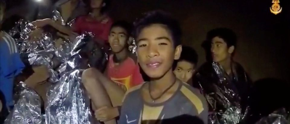 Boys from the under-16 soccer team trapped inside Tham Luang cave covered in hypothermia blankets react to the camera in Chiang Rai, Thailand, in this still image taken from a July 3, 2018 video by Thai Navy Seal. Thai Navy Seal/Handout via REUTERS TV