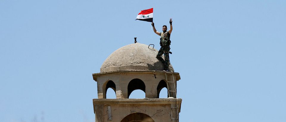 A Syrian army soldier gestures as he holds a Syrian flag in Quneitra, Syria July 27, 2018. REUTERS/Omar Sanadiki