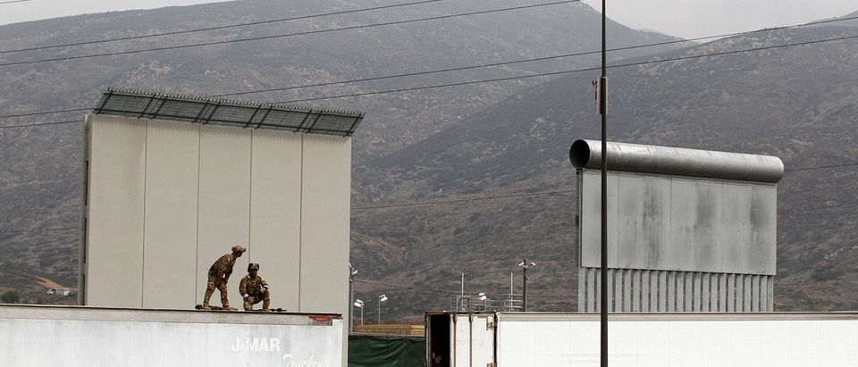 U.S. police officers are seen on top of a truck parked in front of prototypes of U.S. President Donald Trump's border wall, on the U.S. side of the current border fence, in Tijuana, Mexico March 13, 2018. REUTERS/Jorge Duenes