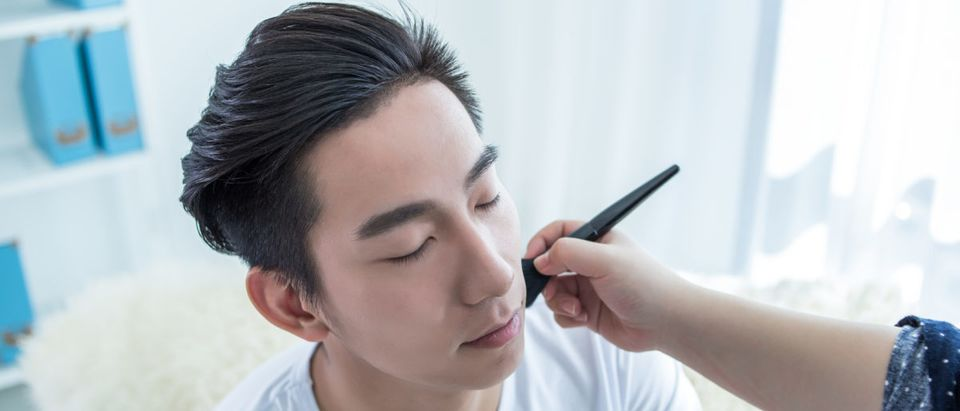 Pictured is a professional makeup artist doing a young man's makeup in the studio. [Shutterstock/ LDWYTN]