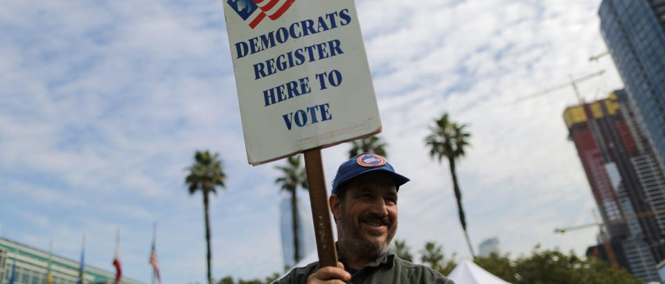 A Democratic Party worker holds up a sign encouraging immigrants who have become new U.S. citizens to sign up to vote in the upcoming midterm elections outside a naturalization ceremony in Los Angeles, California, U.S. March 20, 2018. REUTERS/Lucy Nicholson