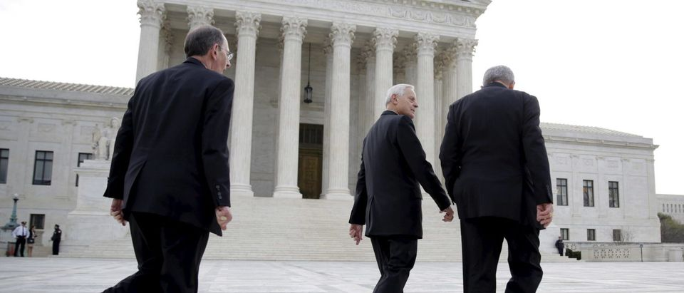 Bishop David Zubik (R) of Pittsburgh and Cardinal Donald Wuerl (C) of Washington walk before before Zubik v. Burwell, an appeal brought by Christian groups demanding full exemption from the requirement to provide insurance covering contraception under the Affordable Care Act, is heard by the U.S. Supreme Court in Washington, March 23, 2016. REUTERS/Joshua Roberts