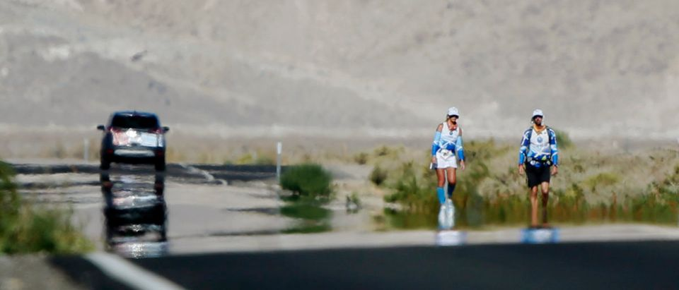 Linda Quick, 60, (L) leans to one side as she walks through a mirage with her pace setter during the Badwater Ultramarathon at the foot of Mount Whitney, California July 16, 2013. The 135-mile (217 km) race, which bills itself as the world's toughest foot race, goes from Death Valley to Mount Whitney, California, in temperatures which can reach 130 degrees Fahrenheit (55 degrees Celsius). Picture taken July 16, 2013. REUTERS/Lucy Nicholson