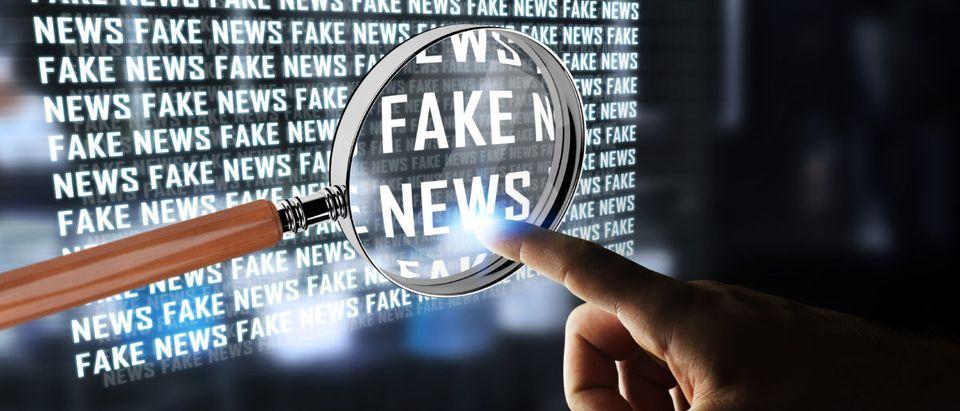 Businessman on blurred background discovering fake news information 3D rendering. (Shutterstock/Sdecoret)