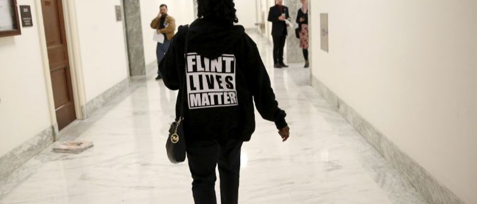 """A woman with a """"Flint Lives Matter"""" shirt walks toward a hearing room where Michigan Gov. Rick Snyder and EPA Administrator Gina McCarthy will testify before a House Oversight and government Reform hearing on """"Examining Federal Administration of the Safe Drinking Water Act in Flint, Michigan, Part III"""" on Capitol Hill in Washington, D.C., U.S. on March 17, 2016. REUTERS/Kevin Lamarque/File Photo"""