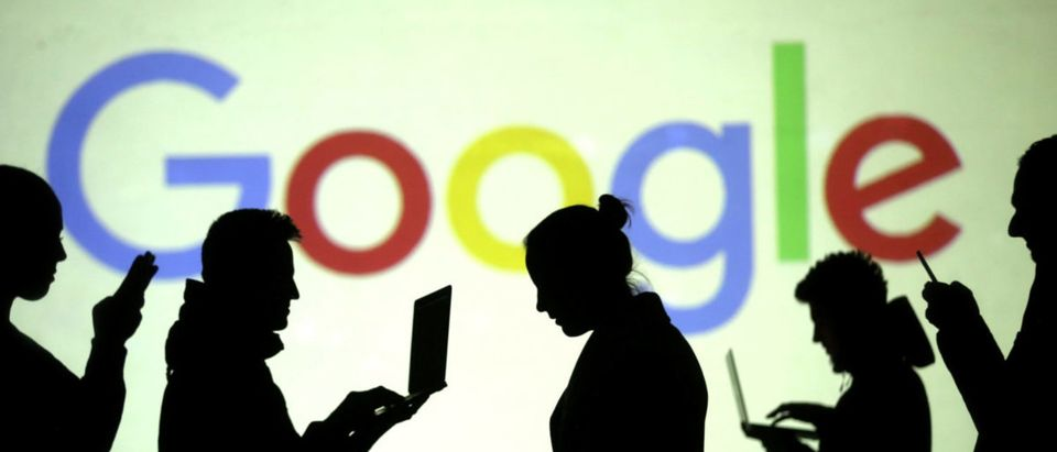 Pictured are silhouettes of laptop and mobile device users in front of a screen projection of the Google logo. Picture illustration taken March 28, 2018. REUTERS/Dado Ruvic/Illustration/File Photo