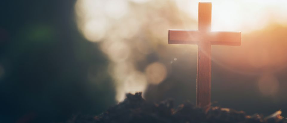 Pictured is a cross on a blurry sunset background. Christian, Christianity, Religion copyspace background. (Shutterstock/ iJeab)