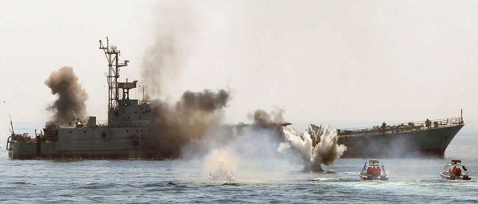 An Iranian warship and speed boats take part in a naval war game in the Persian Gulf and the Strait of Hormuz, southern Iran