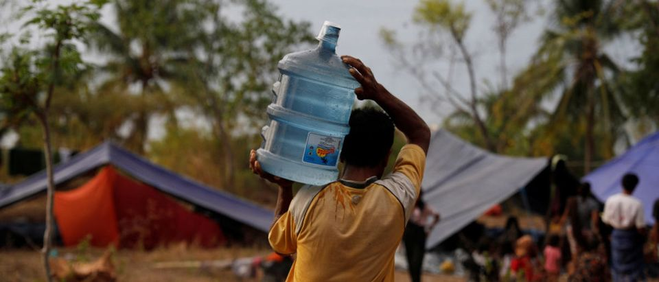 A villager worried about earthquake aftershock and tsunami carries a gallon of drinking water at an empty resort atop a hill in Senggigi beach