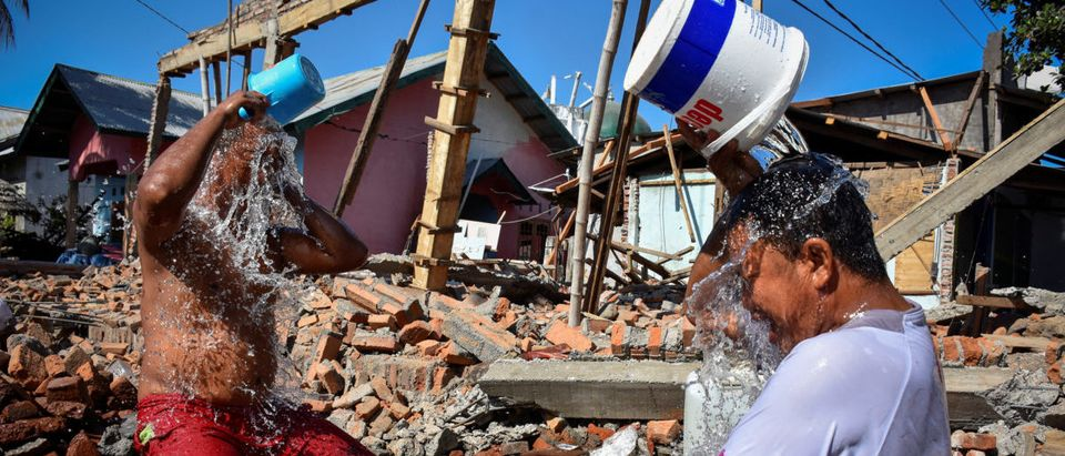 Two men bathe near their homes damaged or destroyed by an earthquake in Kayangan District, Lombok