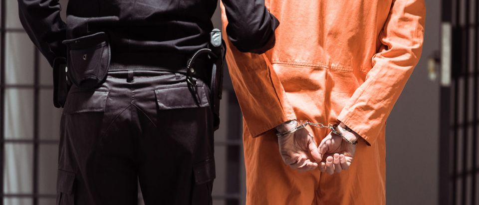 A prisoner is being led to jail. (Shutterstock/ LightField Studios)