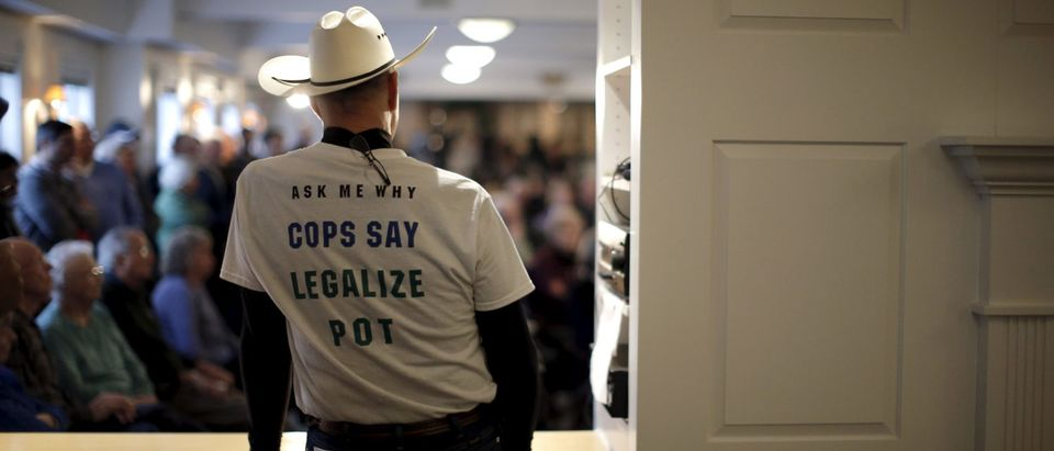 A man wearing a shirt advocating legalized marijuana listens to Republican presidential candidate and New Jersey Governor Chris Christie speak to voters at a town hall campaign stop in Bow, New Hampshire, February 3, 2016. REUTERS/Mike Segar
