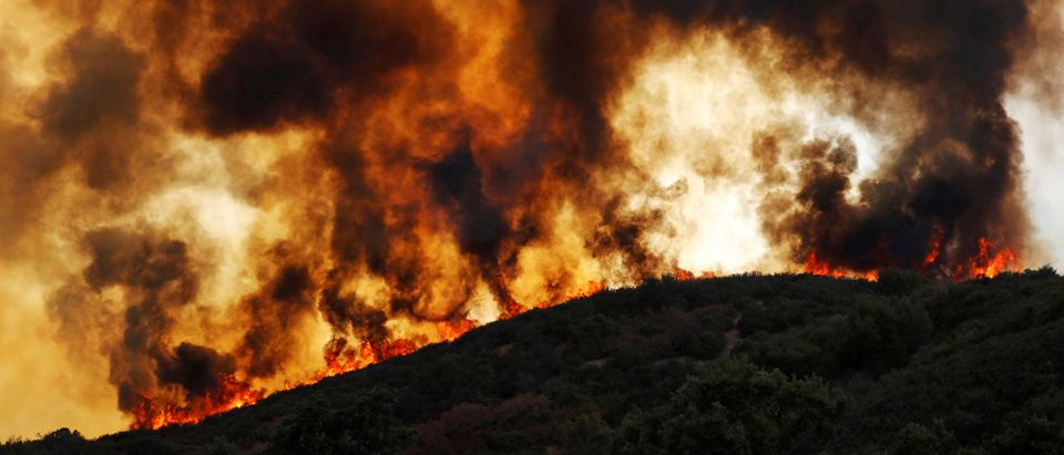 Wind-driven flames roll over a hill towards homes during the River Fire in Lakeport, California