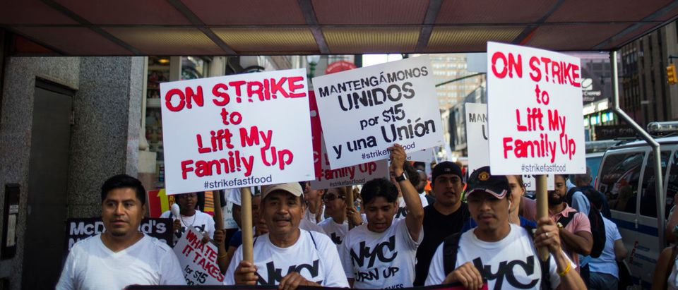 Activists and workers, demanding an increase in minimum wage, march holding placards past a McDonald's fast food restaurant in Manhattan, New York
